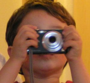 photo of boy with camera blocking his face