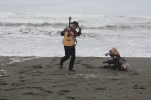 Woman tumbling onto soft sand with guitar held high.
